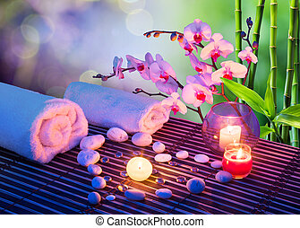 heart of stones massage with candles, orchids, towels and bamboo