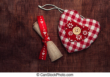 Heart of the fabric in the red cell and a roll of fabric tied with ribbon on a brown wooden background. Valentine's day.