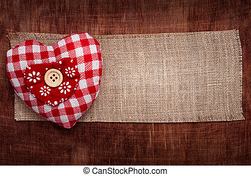 Heart of the fabric in the red cell on a brown wooden background. Valentine's day.