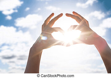 Heart of the fingers against the blue sky and sun