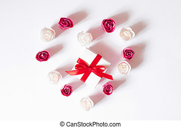Heart of white and pink rose buds on a white background with a gift box