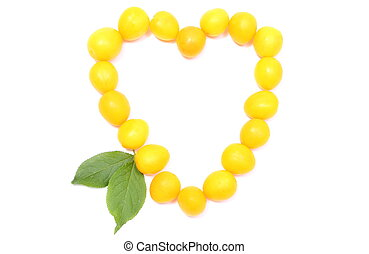Heart of yellow mirabelle on white background
