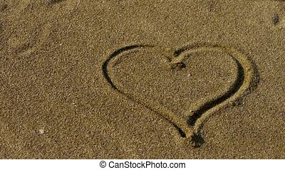 heart on golden sandy beach,wind