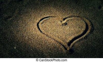 heart on sandy beach, wind blow sand.