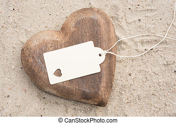Heart on the beach with badge for own text