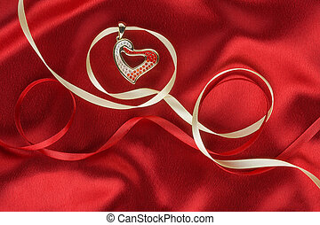 Heart pendant on a background of red silk