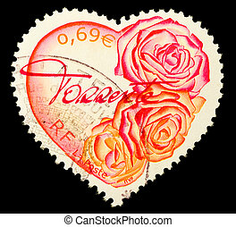 FRANCE - CIRCA 2003: A Heart Shaped Stamp showing pink and red roses isolated on black background, circa 2003