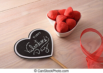 Heart shaped poster with happy valentines day message and jelly sweets and strawberry sugar in heart shaped container. Elevated view.