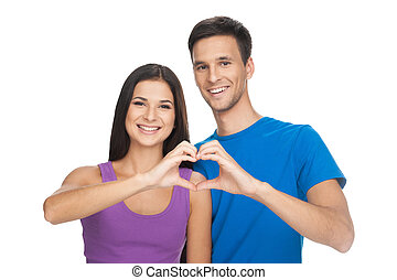 Heart shape. Beautiful young woman and man holding their hands in heart shape and smiling while isolated on white