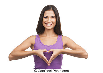 Heart shape. Beautiful young woman holding her hands in heart shape and smiling at camera while isolated on white