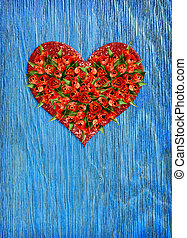 Heart shape bouquet of red tulip flowers in a glitter heart on blue wood