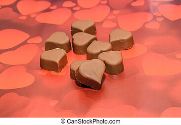 Heart shape chocolate, Valentines Day sweets, brown red background.