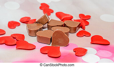 Heart shape chocolate with red hearts, Valentines Day sweets, pink background.