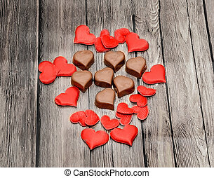 Heart shape chocolate with red hearts, Valentines Day sweets, brown wood background.