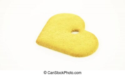 Heart shape cookie rotating on white  background.