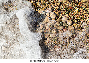 Heart shape created with sea pebbles on a sand and waves. - ...