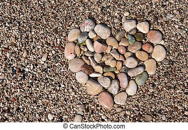 Heart shape created with sea pebbles on a sand. - Heart ...