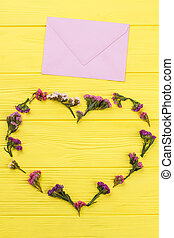 Heart shape flowers and post mail. Yellow wooden table...