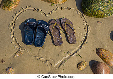 a pair of male and a pair of female footwear standing in heart shape on the beach