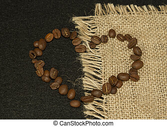 Heart shape from coffee beans on linen cloth on black background