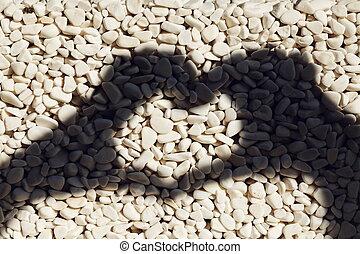 Heart shape hand's shadow on oval pebbles