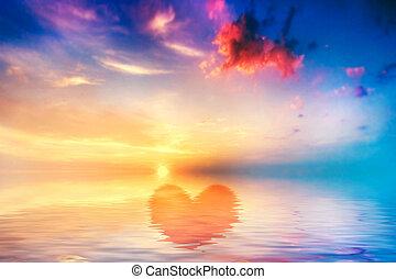 Heart shape in calm ocean at sunset. Beautiful sky