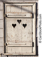 Heart shape look out on wooden door to outhouse. bleach