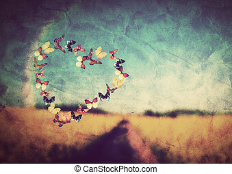 Heart shape made of colorful butterflies on vintage field background