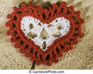 Heart shape made of red textile on wooden base