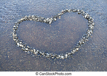 Heart shape made with pebbles on the river