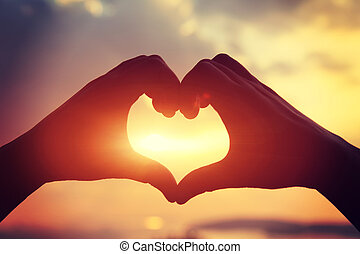Heart shape making of hands against bright sea sunset and...
