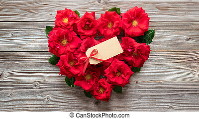 Heart shape of red roses on rustic wooden board