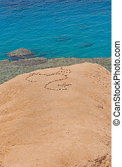 Heart shape on sand made of stones.