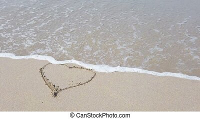 Heart shape on the sand that wiped off by sea wave. 4K love concept clip