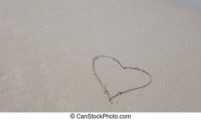 Heart shape on the sand that wiped off by sea wave. 4K love...