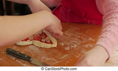 Heart shape pizza cooking daughter and mother homemade toppings closeup