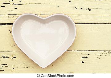 heart shape plate on wooden table%u3000