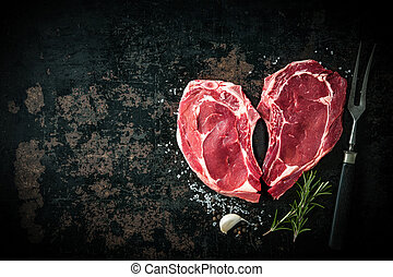 Heart shape raw fresh veal meat steaks with rosemary, pepper...