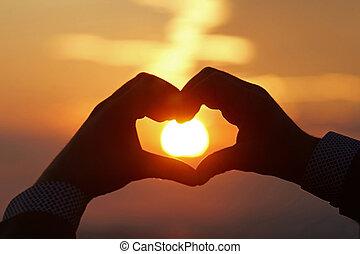 Heart shape silhouette on sunset.