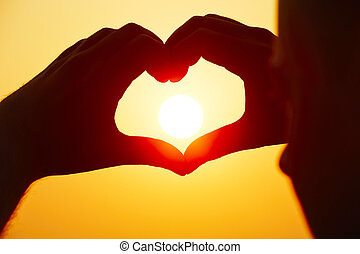 Heart shape - Young man is making heart shape with sun.