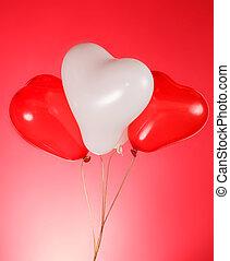 Heart shaped baloons - Three heart shaped baloons on red...