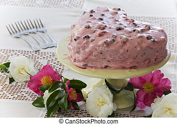 Heart Shaped Berry Cake on a Table with Flowers
