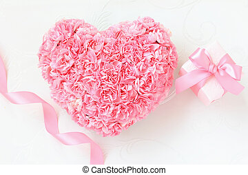 Heart shaped bouquet of pink carnations with gift box on white background