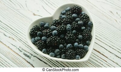 Heart shaped bowl with berries - From above shot of white...