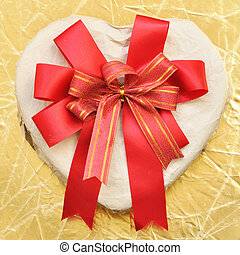 Heart-shaped box with bow on a gold background
