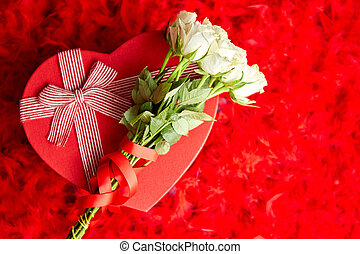 Heart shaped boxed gift, placed on red feathers background...