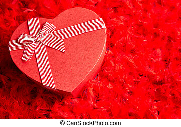 Heart shaped boxed gift, placed on red feathers background. ...