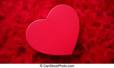 Heart shaped boxed gift, placed on red feathers background....
