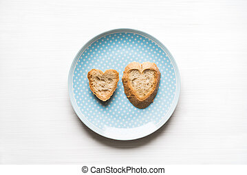 Heart-shaped bread on blue plate love concept