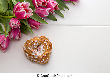 Heart shaped cake and a bouquet of beautiful tulips on wooden background.